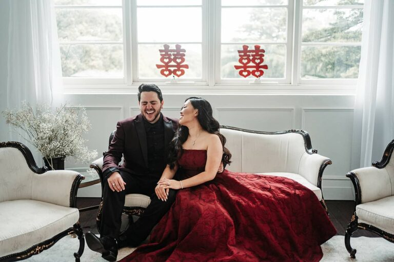 Couple sitting on Sofa in Red Dress and Red Suit for thier Tea Ceremony before wedding