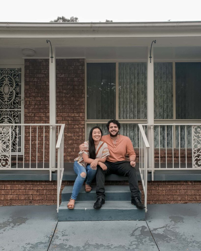 Couple sitting on front steps of their new house